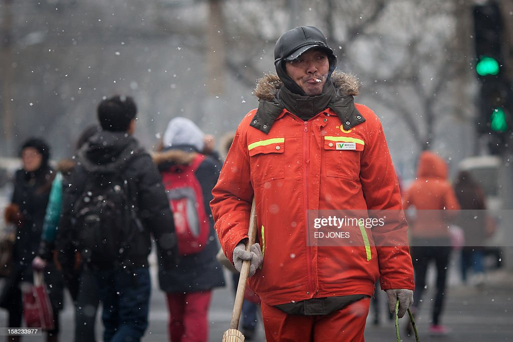 A street sweeper smokes a cigarette as he crosses a road during snowfall in Beijing on December 12, 2012. Snowfall hit the Chinese capital with seasonal minus temperatures forecast to bring more later in the week. AFP PHOTO / Ed Jones