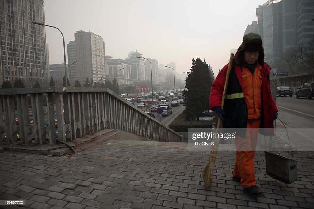 A street sweeper stands by a busy road in Beijing on January 22, 2013. Beijing has the worst traffic jams in the world, as record traffic levels take their toll on people's health, productivity and social lives, a study by IBM reported early January. Beijing and Mexico City scored 99 out of 100 in IBM's commuter pain index, followed by Johannesburg, Moscow and New Delhi. AFP PHOTO / Ed Jones