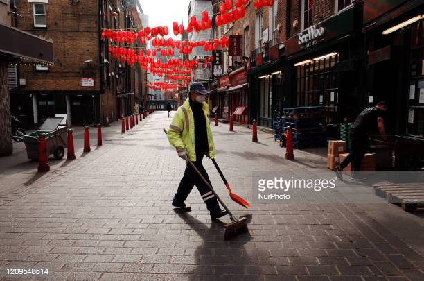 Street sweeper walks across a near-deserted Lisle Street in Chinatown in London, England, on April 8, 2020. With the country not predicted to reach...