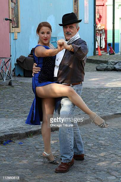 A street tango dancer left poses with a tourist in Buenos Aires Argentina