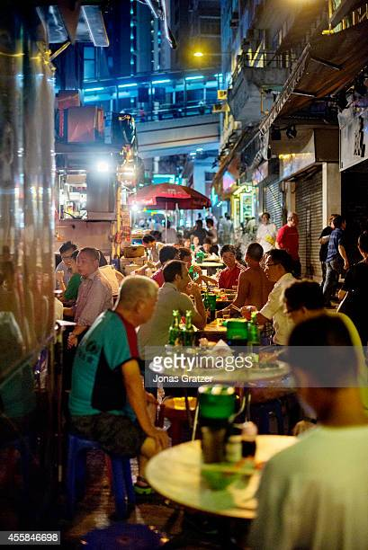 A street that is packed with both foreigners and locals who are enjoying the street food that is laid out at night in the alleyways