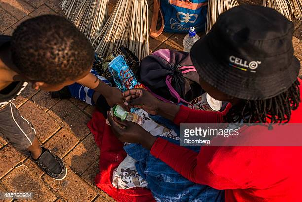 A street trader selling brooms holds a bundle of rand banknotes in this arranged photograph in Johannesburg South Africa on Wednesday Aug 26 2015...