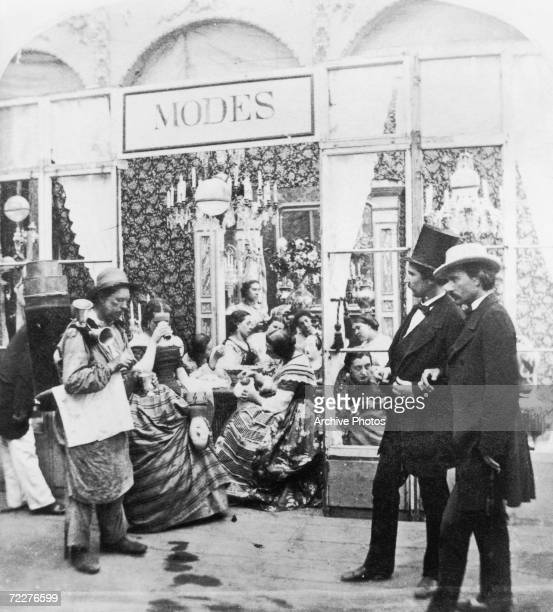 A street trader selling drinks outside a clothes shop in Paris circa 1865