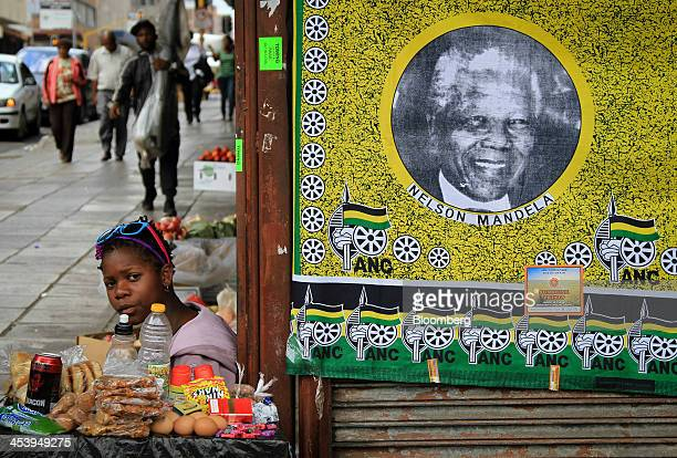 A street trader sells snacks beside a fabric sheet commemorating the life of the former South African President Nelson Mandela following the...