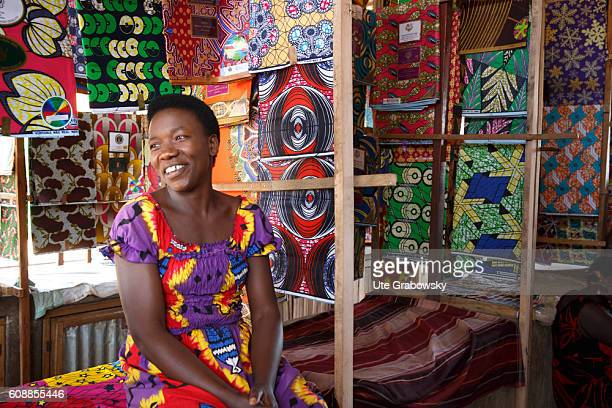 A street trader sells traditional fabrics in a market hall on August 11 2016 in Kigali Rwanda
