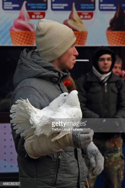 Street trader waits for business outside Khreshchatyk metro station, hoping to rent his doves to idealistic revolutionaries for a photo before they...