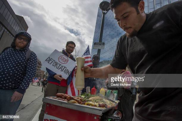 A street vender sells hot dogs to demonstrators during the Immigrants Make America Great March to protest actions being taken by the Trump...