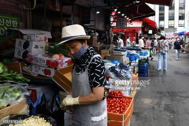 Street vender wears a mask to prevent the coronavirus at the Namdaemun market on July 21, 2020 in Seoul, South Korea. With the number of daily local...