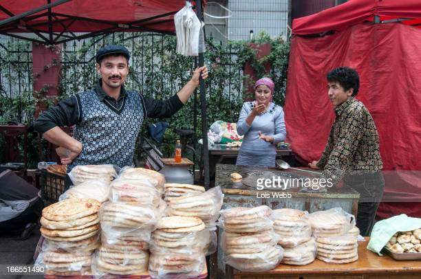 CONTENT] A street vendor and his wife sell traditional round flat bread at the Friday muslim market in Jing'an district in Shanghal The Uyghur...