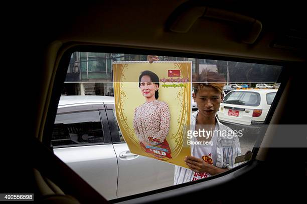 A street vendor approaches a taxi to sell merchandise featuring Aung San Suu Kyi Myanmar's opposition leader and chairperson of the National League...
