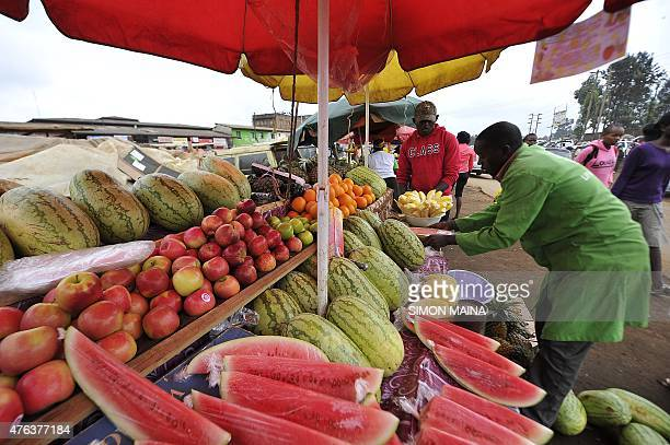 A street vendor arranges fruits in a street market in Kabete on the outskirts of Nairobi on June 8 2015 The city knows a recent increase of large...