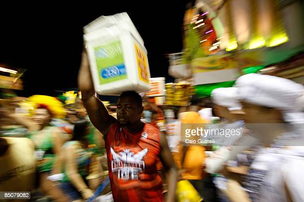 A street vendor carries a box of beers in the BarraOndina street carnival track on February 24 2009 in Salvador Brazil