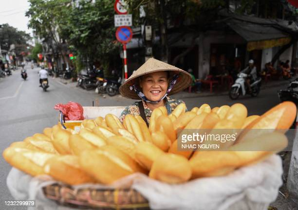 Street vendor carries baguettes for sale on her bicycle along a street in Hanoi on April 14, 2021.