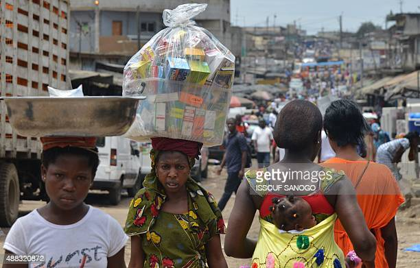 A street vendor carries medicines upon her head in the streets of the popular district of Adjame in Abidjan on September 15 2015 AFP PHOTO / ISSOUF...