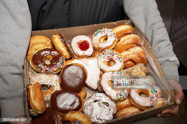 Street vendor carrying box of doughnuts, mid section, elevated view