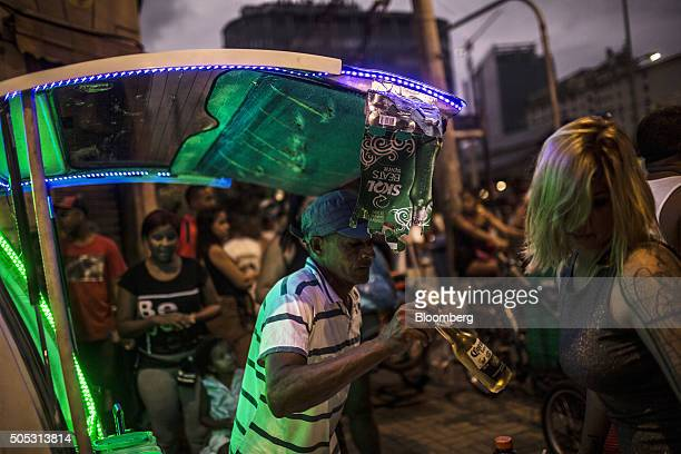 A street vendor center holds a bottle of beer for sale during a street parade ahead of Rio's 2016 Carnival in Rio de Janeiro Brazil on Saturday Jan...