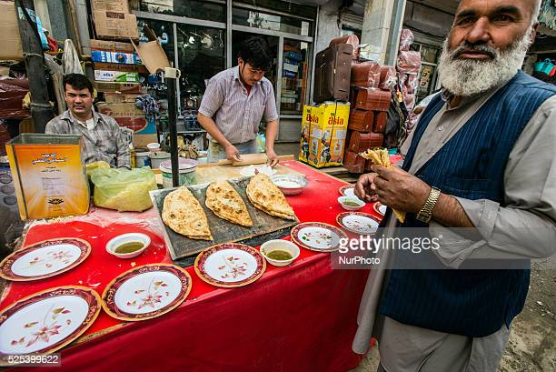 Street vendor cooks and sells bolani on Bazaar in Old city of Kabul Afghanistan