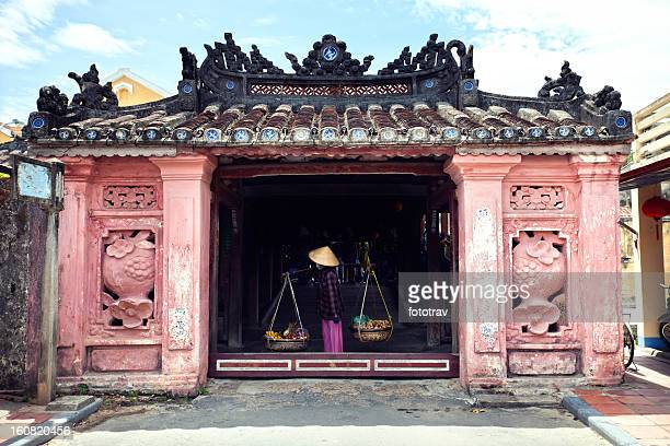 street vendor crossing the japanese bridge in hoi an, vietnam - hoi an stock pictures, royalty-free photos & images