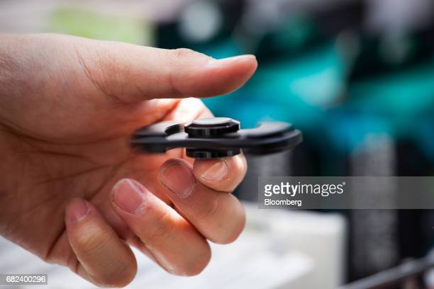 A street vendor demonstrates a fidget spinner in New York US on Friday May 12 2017 The fidget spinner is a toy that sits like a propeller on a...