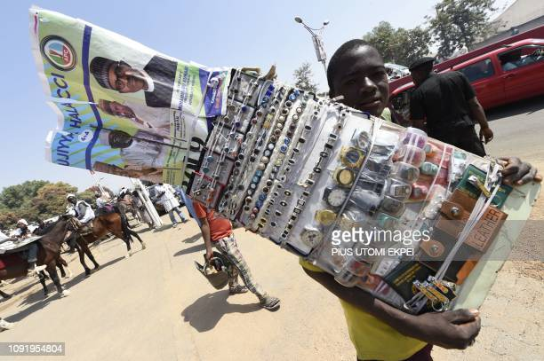 TOPSHOT A street vendor displays a picture of ruling All Progressives Congress party's candidate President Mohammadu Buhari during a presidential...