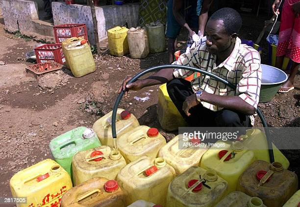 A street vendor fills his plastic containers with water 17 December 2003 in a street of the popular and residential area of Simbaya in the outskirts...