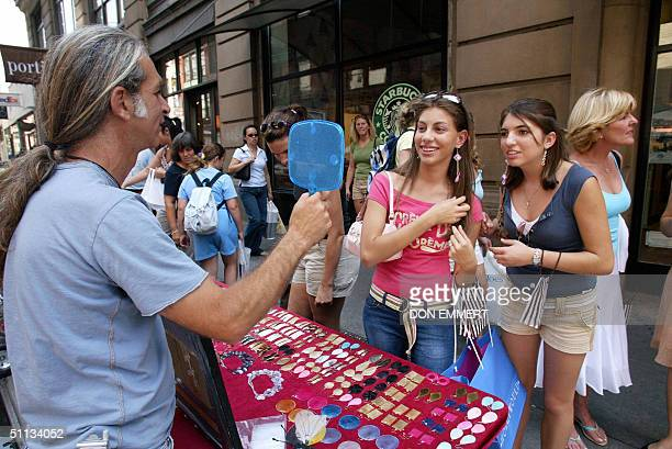 A street vendor holds up a mirror for Marina Lopez and Ashley Marchante both of Miami trying on earrings while on a shopping tour 29 July 2004 in New...