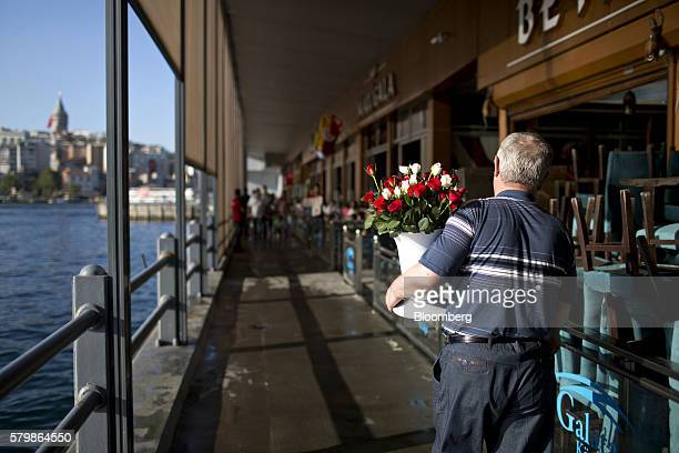 A street vendor looks for customers to sell his roses to on the Galata bridge in Istanbul Turkey on Friday July 22 2016 Aiming to limit the economic...
