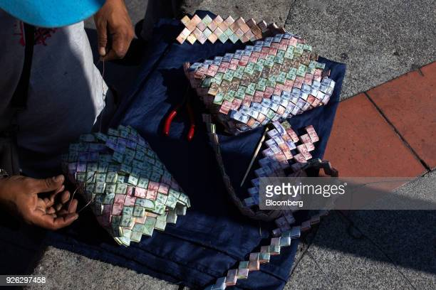 A street vendor make a purse with Bolivar banknotes to sell in Caracas Venezuela on Thursday March 1 2018 In hyperinflationary Venezuela paper money...
