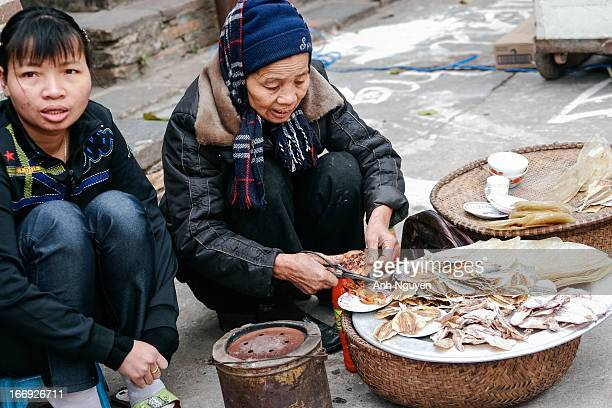 Street vendor of dried seafood - a popular kind of street food in populated places in North Vietnam . Dong Ky village - Bac Ninh Province- North...
