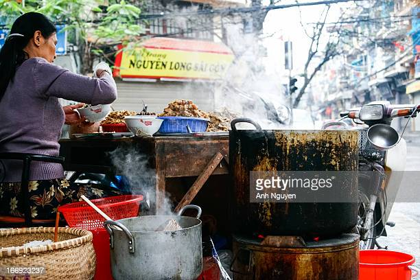 Street vendor of fish vermicelli with hot boiling pots around her - Old Quarter of Hanoi, Vietnam. Fish vermicelli is a popular kind of street food...