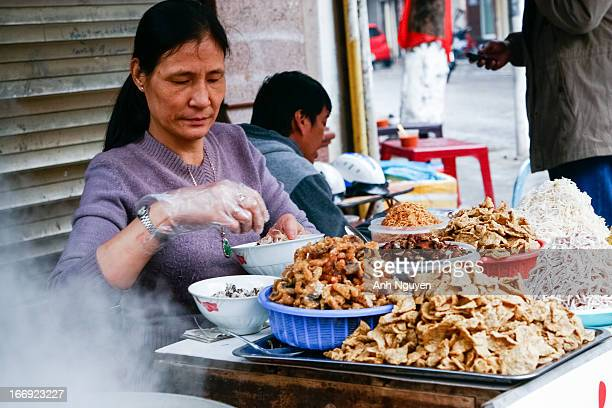 Street vendor of fish vermicelli with plates of ingredients - Old Quarter of Hanoi, Vietnam. Fish vermicelli is a popular kind of street food that...