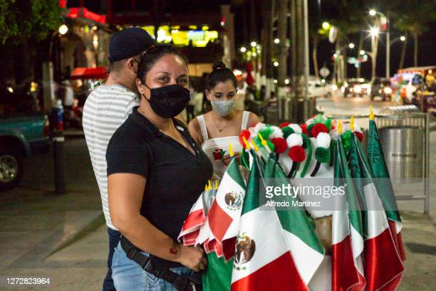 A street vendor of flags poses for a portrait on the Malecon de La Paz as part of the Independence Day celebrations on September 15 2020 in La Paz...
