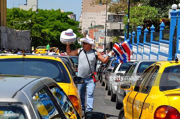 A street vendor offers hats and Costa Rican flags while walking between hundreds of pirate taxis parked in front of the Legislative Assembly building...