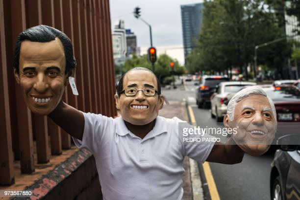 TOPSHOT A street vendor offers masks of Mexican presidential candidates Jose Antonio Meade Ricardo Anaya and Andres Manuel Lopez Obrador for sale in...