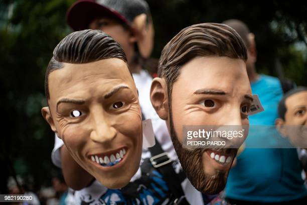 A street vendor offers masks of Portuguese forward Cristiano Ronaldo and Argentinian forward Lionel Messi for sale in a street in Mexico City on June...