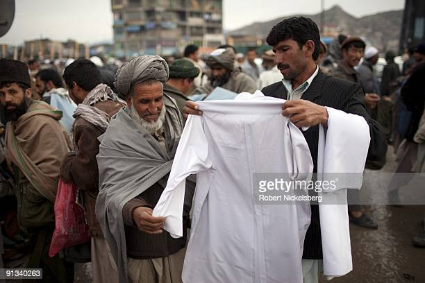 A street vendor offers to sell a shalwarkamiz April 6 2009 in the downtown market district of Kabul Afghanistan Kabul has an estimated population of...