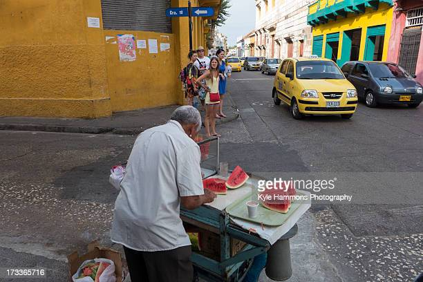 Street vendor prepares slices of fresh watermelon for tourists and locals alike on the streets of the old town in Cartagena, Colombia