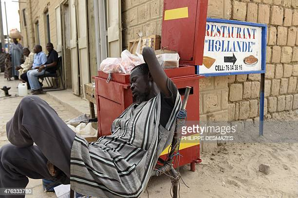A street vendor rests as a sign shows a restaurant named after the French president on June 6 2015 in Timbuktu during the joint operation 'La Madine...