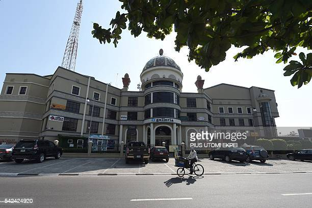 A street vendor rides a bicycle past Silverbird Galleria which hosts cinemas and shopping malls in Lagos on June 23 2016 Nigerian media entertainment...