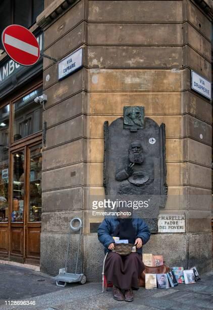 street vendor selling cd's in front of a statue at the corner of a building. - emreturanphoto fotografías e imágenes de stock