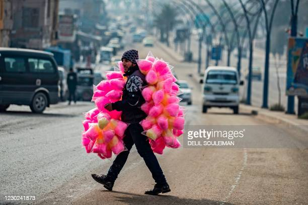 Street vendor selling cotton candy crosses a road in the northern Syrian city of Raqa, the former Syrian capital of the Islamic State group, on...