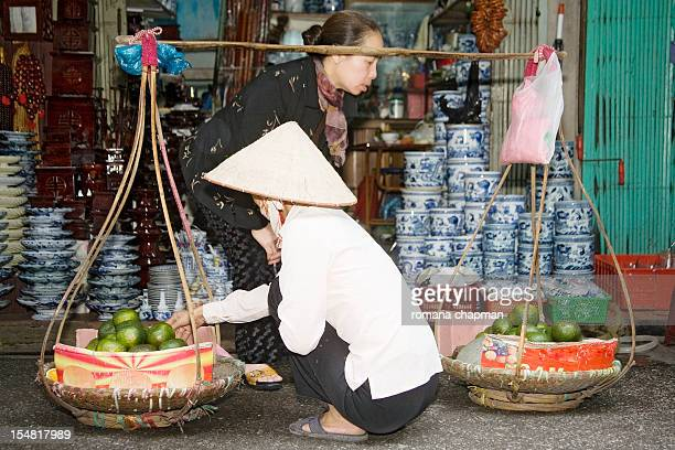 street vendor selling fruit from bamboo baskets