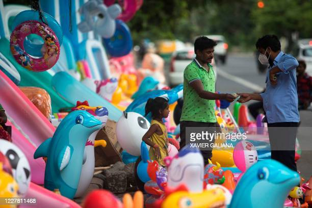 Street vendor selling inflatable pools and toys closes a deal at his stall along a road in New Delhi on July 28, 2020.