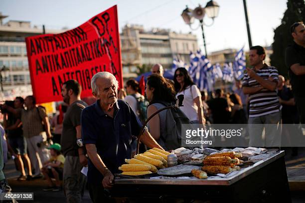 A street vendor selling roasted corn cobs passes antibailout protestors on Syntagma Square during a demonstration outside the Greek parliament in...