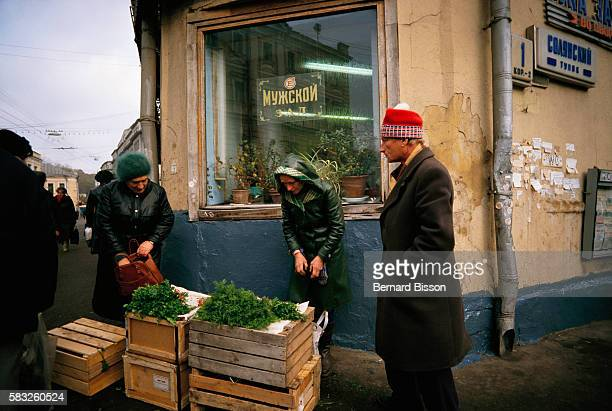 A street vendor sells a few green vegetables displayed on top of wooden boxes at a Moscow street corner during the Gorbachev era