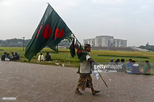A street vendor sells Bangladeshi national flags in front of the national parliament building in Dhaka on December 13 ahead of the country's 44th...