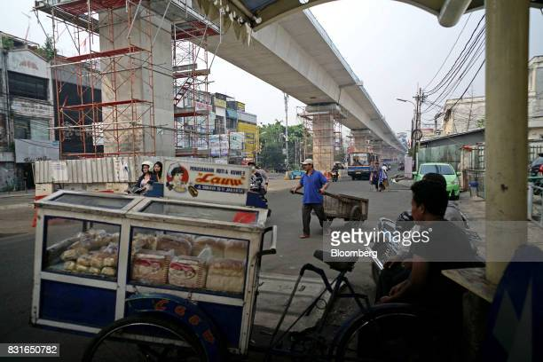 A street vendor sells bread from a cart in front of an elevated track for the Jakarta Mass Rapid Transit as it stands under construction in Jakarta...