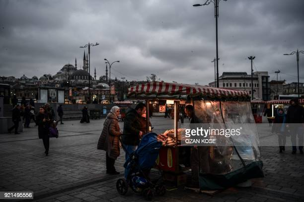A street vendor sells chestnuts near Galata Bridge with Suleymaniye Mosque in the background during a cloudy day in Eminonu District in Istanbul on...