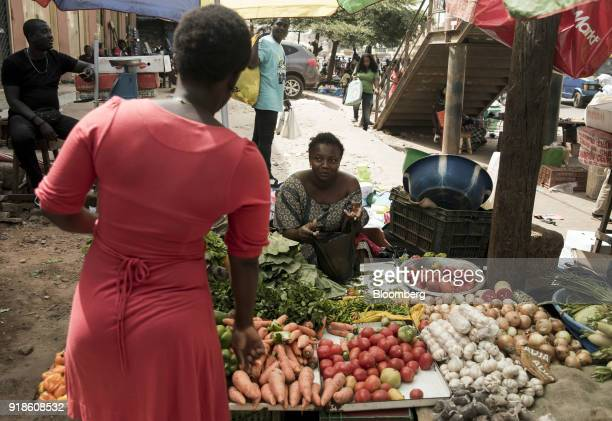 A street vendor sells fresh fruit and vegetables at Bandim market in Bissau GuineaBissau on Tuesday Feb 13 2018 The International Monetary Fund said...