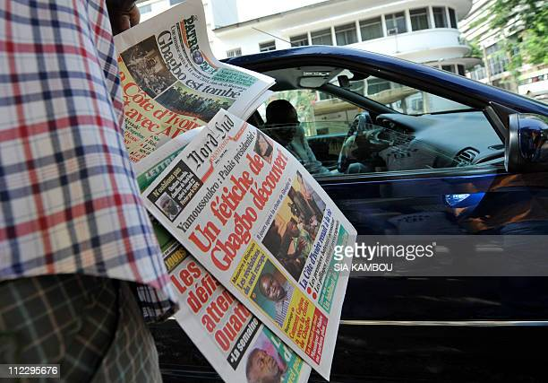 A street vendor sells newspaper to a motorist on April 18 in the Plateau the buisiness district of Abidjan Ouattara's government ordered civil...